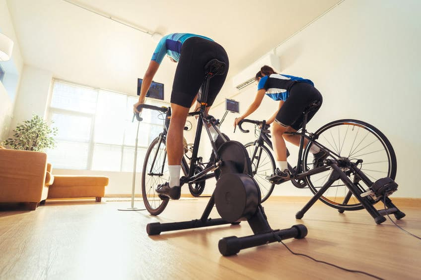 To personer på cykeltræner hjemme i stuen.