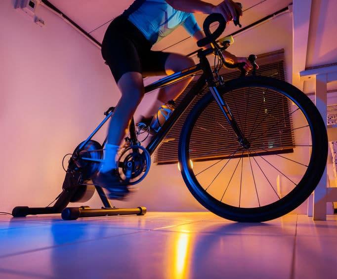 Mand på cykeltræner cykler med Zwift.